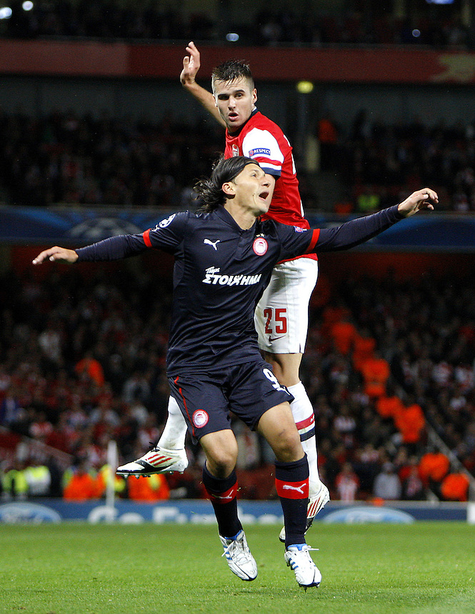 Arsenal's Carl Jenkinson clashes with Olympiakos' Marko Pantelic ..Football - UEFA Champions League Group B - Arsenal v Olympiakos FC - Wednesday 3rd October 2012 - Emirates Stadium - London..