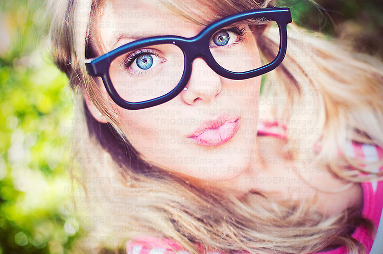 Close up of young woman with blonde hair pouting wearing large black glasses