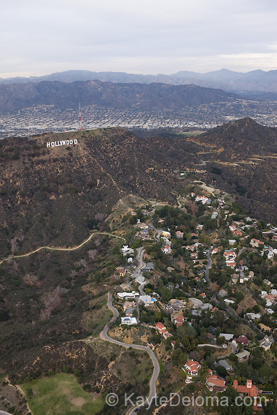 Aerial view of the Hollywood Sign on Mt. Lee in Griffith Park with the Hollywood Hills in the foreground and the San Gabriel Valley and San Gabriel Mountains in the background, seen from Airship Ventures Hollywood Studios Zeppelin Air Tour, Los Angeles, CA