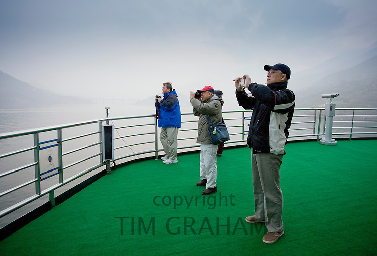 Tourists take photographs from the deck of a Victoria Line Cruise Ship, Yangze River, China