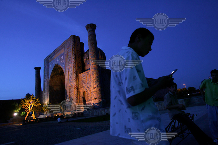 A young man using a mobile phone in the Registan. Behind him is the Sherdor Madrasah, one of the three great buildings that enclose the square.