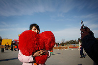 CHINA. A woman holding a heart during Chinese New Year in Ditan Park in Beijing.  Chinese New Year, or Spring Festival, is the most important festival and holiday in the Chinese calendar In mainland China, many people use this holiday to visit family and friends and also visit local temples to offer prayers to their ancestors. The roots of Chinese New Year lie in combined influences from Buddhism, Taoism, Confucianism, and folk religions.  2008.