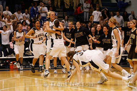 Skyline High School's basketball team erupts off the bench after Liz Johnson (white headband being hugged) hit a last second shot to beat Davis and send Skyline to Saturday's State Championship game. Hugging Johnson is teammate Jenteal Jackson. Taylorsville - Skyline defeats Davis High School with a shot at the buzzer, 5A Girls State Basketball Championships at Salt Lake Community College.