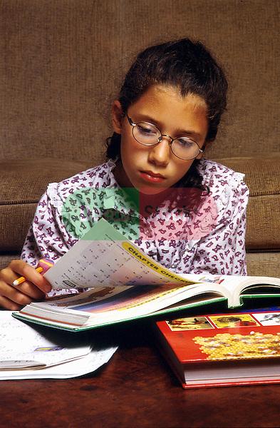 young girl wearing eyeglasses studying, doing homework