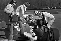 A film crew records author George Plimpton receiving final advice from driver Bobby Rahal and owner Jim Trueman before testing an IndyCar at Mid-Ohio Sports Car Course in 1982.