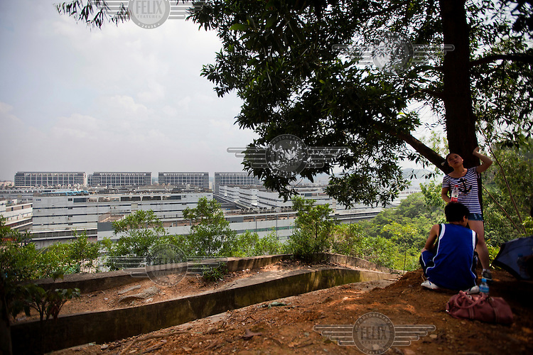Foxconn workers relax in the hills above the Guanlan factory on a Sunday excursion. The taller blocks on the horizon are the in-house factory dormitories. Foxconn is a Taiwanese technology company that makes products for Apple and Sony among others and is the largest private sector employer in China.