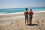 Model released brother and sister twins stand on sandy beach looking out to sea, Rhodes, Greece,