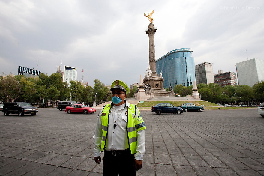 27 April 2009 - Mexico City, Mexico - A traffic officer wears a surgical mask to protect himself from the swine Flu. In Mexico City, things a noticably quieter, the normally busy and crowded plazas, parks and food stalls have been much more tranquil over the past couple days. Lots of people stay home and public places shut due to swine flu. Photo credit: Benedicte Desrus / Sipa Press