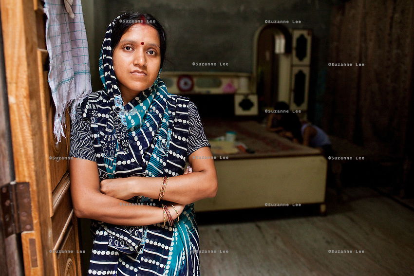 Seema Gupta (aged 34, foreground) poses for a portrait while her sons play in the room in her shophouse in Ghaziabad, Uttar Pradesh, India. Seema Gupta had a tubectomy done on 9 June 2011 for family planning while her husband, Ramesh Chandra Gupta (38), wasn't aware of the option and benefits of non-scalpel vasectomy (NSV). They run a roadside sweets shop at the front of their house and chose to have a family planning surgery done as they did not want to compromise the quality of life for their two children. While Ramesh wanted only 1 child, both his mother and Seema pushed for a 2nd child. Photo by Suzanne Lee / Panos London