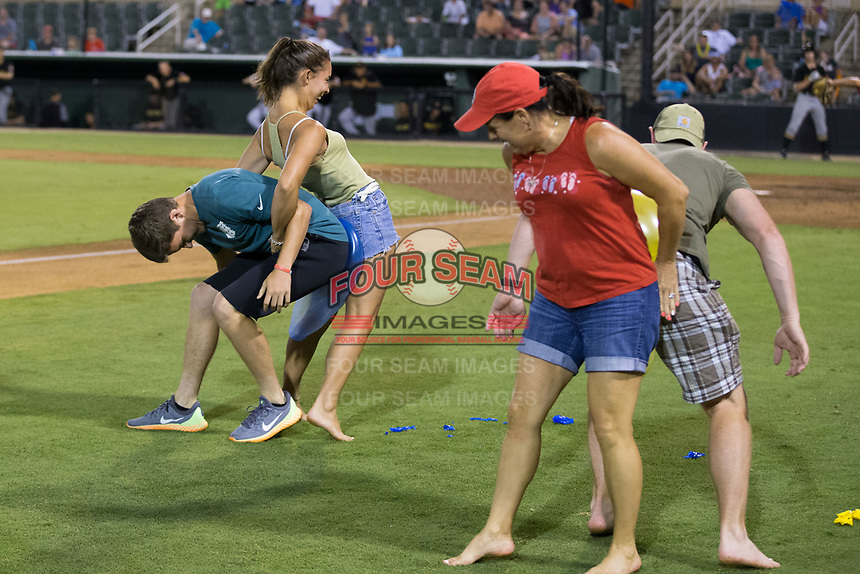 Fans compete in a between innings contest where they have to use their bodies to pop ballons at Kannapolis Intimidators Stadium on June 17, 2017 in Kannapolis, North Carolina.  The Power defeated the Intimidators 6-1.  (Brian Westerholt/Four Seam Images)