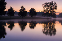 A light mist rises off a lake at dawn.