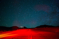 Incredible star-filled sky over a road lit with red light, Big Island.
