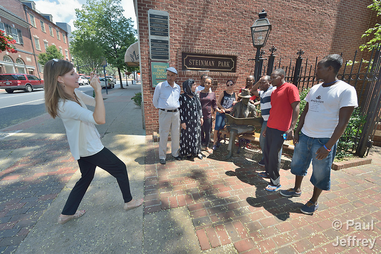Penny Gushiken (left) takes a photo of her cultural orientation class for newly arrived refugees in downtown Lancaster, Pennsylvania. The class was engaged in a scavenger hunt of sorts, tasked with finding people engaged in specific activities such as listening to music, talking on the phone, and taking out trash. In this case, the class was supposed to find someone reading. They found a statue of a man reading, so Gushiken took a photo of the group posing with him. The class is sponsored by Church World Service. <br /> <br /> Photo by Paul Jeffrey for Church World Service.