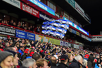 A Bath supporter in the crowd waves a giant flag in support. Aviva Premiership match, between Gloucester Rugby and Bath Rugby on March 26, 2016 at Kingsholm Stadium in Gloucester, England. Photo by: Patrick Khachfe / Onside Images