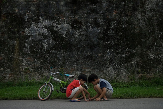 Two Vietnamese boys play a game in the street in Hue, Vietnam.