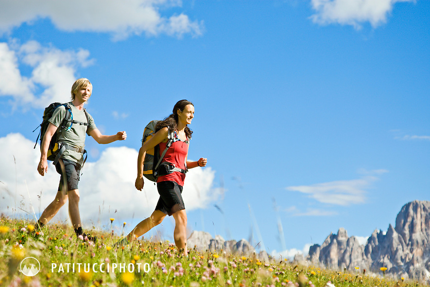 Norbert Notdurfter and Patrizia Taibon hiking through spring wild flowers in the Italian Dolomites