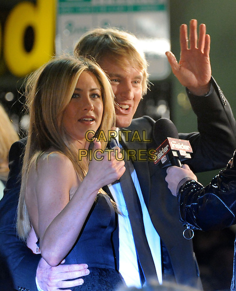 """JENNIFER ANISTON & OWEN WILSON.The Twentieth Century Fox World Premiere of """"Marley & Me"""" held at The Mann Village Theatre in Westwood, California, USA. .December 11th, 2008 .half length black grey gray strapless silk satin top suit jacket interview microphone hand palm waving thumb up ring  .CAP/DVS.©Debbie VanStory/Capital Pictures."""
