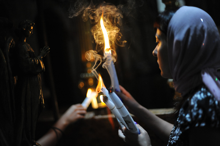 Women pilgrims light candles as they visit the Church of the Holy Sepulchre, in Jerusalem's old city.