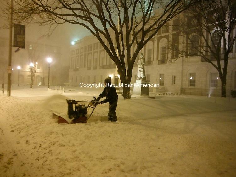 WATERBURY CT, 08 FEB 13-020913AK01-  A man clears snow in front of Waterbury City Hall Friday night. Anne Karolyi/ Republican-American