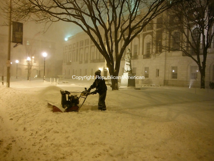 WATERBURY CT, 08 FEB 13-020913AK01-  A man clears snow in front of Waterbury City Hall Friday night. Anne Karolyi/ Republican-American