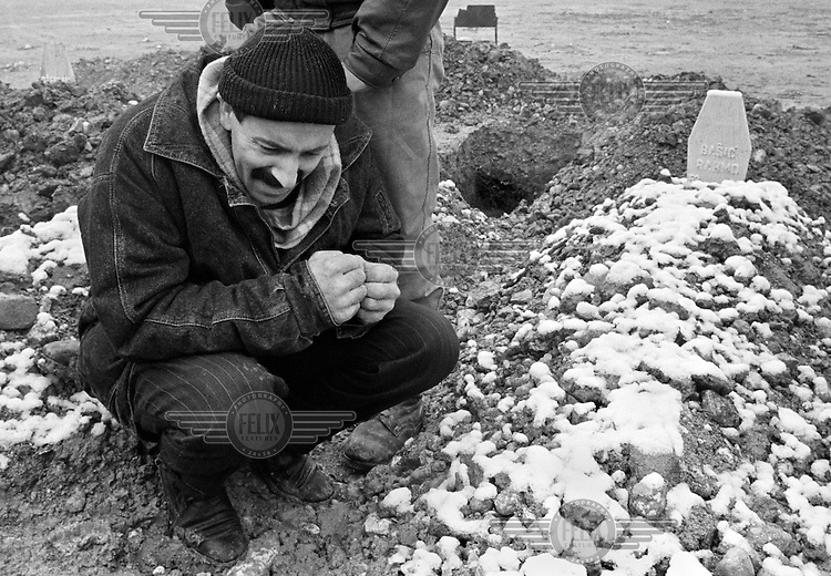 A Bosnian man grieves at a friend's grave in a makeshift cemetery in a soccer field in Sarajevo on December 10, 1993.