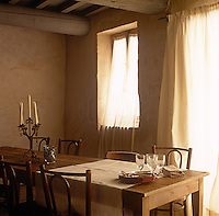 A simple dining room with plain walls and a grey painted ceiling. The room is furnished with a long dining table and bentwood chairs. Sheer curtains at the windows soften the light.