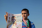 The son of Mohammad al-Jadili, a Palestinian medic died of wounds he sustained during a protest at the Israel-Gaza border fence, holds his father photo during the tents protest where Palestinians demand the right to return to their homeland at the Israel-Gaza border, in Jabalia in the northern Gaza Strip, June 14, 2019. Photo by Ramez Haboub