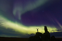 Man stands on a granite tor while the aurora swirls overhead. Bering Land Bridge National Preserve, Seward Peninsula, Alaska.