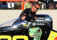 Jul. 18, 2014; Morrison, CO, USA; A crew member pushes NHRA top fuel driver Richie Crampton back after the burnout during qualifying for the Mile High Nationals at Bandimere Speedway. Mandatory Credit: Mark J. Rebilas-