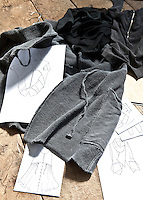Hand-drawn designs lie amongst a pile of casual clothes on a rustic table top