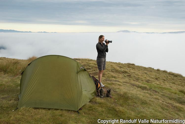 Dame filmer at tåka ligger i dalbunnen. ---- Girl filming mist.