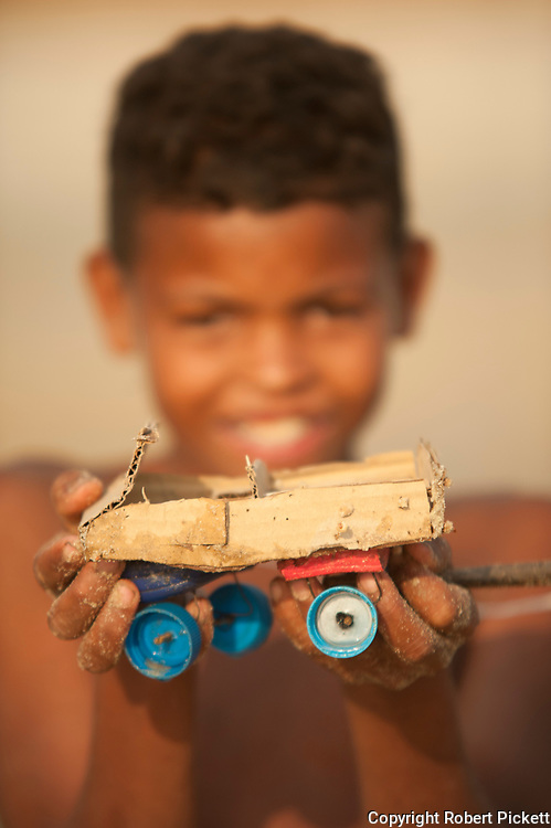 Young boy showing toy car made from recycled materials, Ifaty, Madagascar