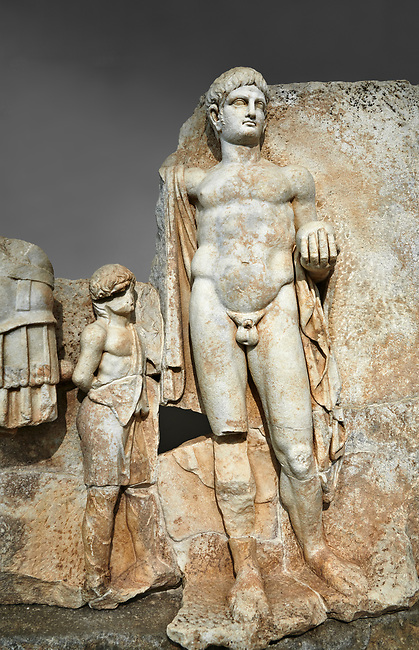Close up of a Roman Sebasteion relief  sculpture of Emperor Nero with captive, Aphrodisias Museum, Aphrodisias, Turkey.  Against a grey background.<br /> <br /> Naked warrior emperor Nero holds the orb of world rule in one hand and crowns the military trophy with the other. Between the trophy and the emperor stands a bound captive boy. He wears long barbarian trousers and looks up at Nero.
