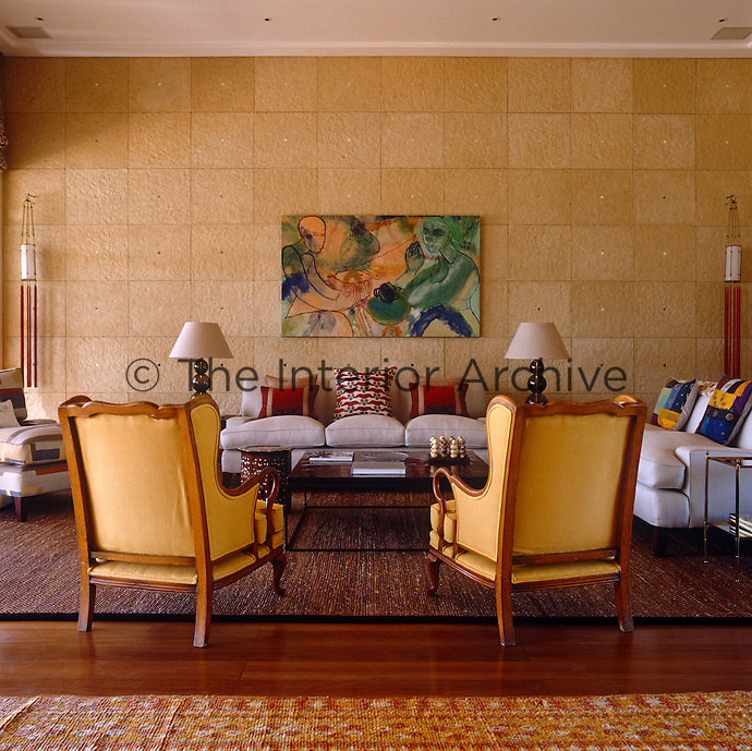 Two elegant wing-backed armchairs upholstered in warm butter-yellow blend with the mellow stone wall in the living room