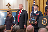 Valerie Nessel, widow of Technical Sergeant John A. Chapman, United States Air Force, left, stands with US President Donald J. Trump, center, makes remarks as she accepts the Medal of Honor posthumously from the President during a ceremony in the East Room of the White House in Washington, DC on Wednesday, August 22, 2018.  Sergeant Chapman is being honored for his actions on March 4, 2002, on Takur Ghar mountain in Afghanistan where he gave his life to save his teammates.<br /> Credit: Ron Sachs / CNP