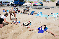 Sisters Chloe, 15, (center) and Amelie Lachance-Soulard, 16 (right), of Ottawa, Canada, and cousin Simone Soulard, 14, lay buried under sand sculptures of mermaid tails at Herring Cove Beach in the Cape Cod National Seashore outside of Provincetown, Mass., USA, on Fri., July 1, 2016. Their aunt Claudine Soulard, of Montreal, (standing, right) and the sisters' mother Pascale Lachance, of Ottawa, (kneeling, left) helps sculpt the sand. Portions of the parking lot have been closed after land eroded during storms earlier this year. This was the girls' first visit to the area.
