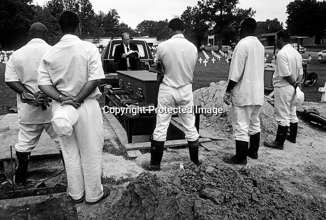 A priest holds a ceremony for a diseased Death Row inmate that hasn't been claimed by his family on April 23, 1997 in Huntsville, Texas USA. About 1300 prisoners from the state of Texas are buried here, among them 200 who died on Death Row. Texas has about 450 prisoners on death row. The state leads all records in executing people around the US. The prisoners are executed by lethal injection. (Photo by: Per-Anders Pettersson).......