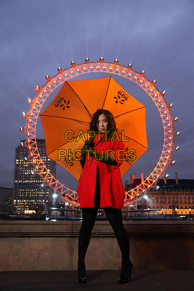 MYLEENE KLASS.TV presenter Myleene Klass stands in front of the EDF Energy London Eye as it is illuminated to mark the launch of EDF Energy's three-year partnership with the London Eye. As Britain's largest producer of low carbon electricity, EDF Energy will be helping to reduce the London Eye's carbon footprint. EDF Energy will also guarantee that every single unit of energy used by the EDF Energy London Eye is matched with energy generated from low carbon sources.*Editorial Use Only*.January 25th, 2011.england orange umbrella red coat jacket black tights gloves .CAP/PLF.Supplied by Capital Pictures.