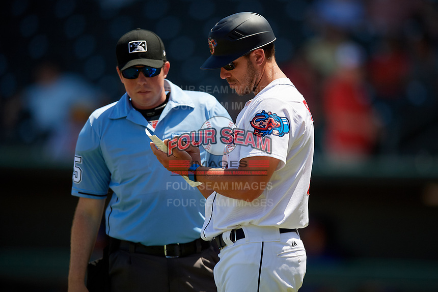 Jacksonville Jumbo Shrimp manager Kevin Randel (11) makes changes with home plate Umpire Austin Jones during a Southern League game against the Tennessee Smokies on April 29, 2019 at Baseball Grounds of Jacksonville in Jacksonville, Florida.  Tennessee defeated Jacksonville 4-1.  (Mike Janes/Four Seam Images)