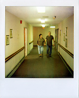 Carolyn Eberspecher walks her husband, Mike, to his room as they enter the Douglas Care Center for Mike's first day as a resident...Alzheimers.  Douglas, Wyoming..Mike Eberspecher was diagnosed at 60 with early onset Alzheimers.  The disease, a subset of dimentia, gradually impairs the brain's ability to form new memories, simultaneously undoing connections that make up old memories.  Patients generally experience memory loss from the present, backwards.  Early onset Alzheimers tends to progress quicker in younger patients. ..Carolyn Eberspecher has been caring for her husband, Mike, for the last five years.  Over time, he has gradually lost his ability to care for himself and relies on her for most of his needs.  In April of 2010, Carolyn will place her husband in an Alzheimer's care unit in the town's nursing home.  .Carolyn Eberspecher attends church in Douglas, Wyoming.  Carolyn and Mike attend separate churches.  After Mike was diagnosed with Alzheimers, he returned to attending Mormon church, a tradition which had fallen by the wayside for most of his adult life.