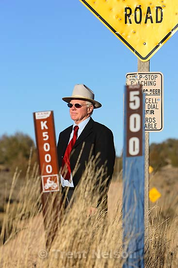 Kane County Commissioner Mark Habbeshaw at the intersection of Johnson Canyon Road and Skutumpah Road in the Grand Staircase National Monument, where the BLM and Kane County have placed conflicting signs. Kane County's sign (on left) indicates OHV/ATV access, which the BLM disputes.<br />