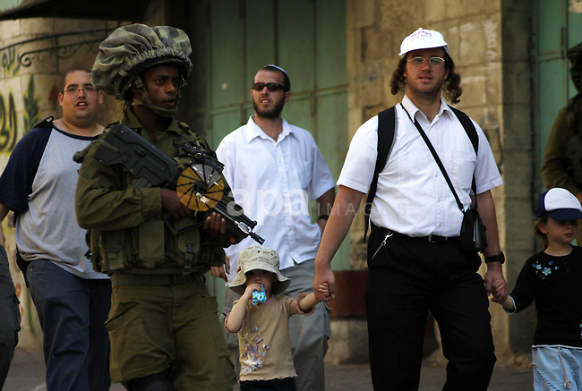 Israeli settlers are escorted by Israeli troops inside the old city of the West Bank  town of Hebron on 26 September 2010. A large group of right-wing Jews toured the area with Israeli soldiers escort on the day when the government's settlement freeze is due to expire. Thousands of right-wing Jews are expected in a West Bank settlement later today to begin building. Photo by Mamoun Wazwaz