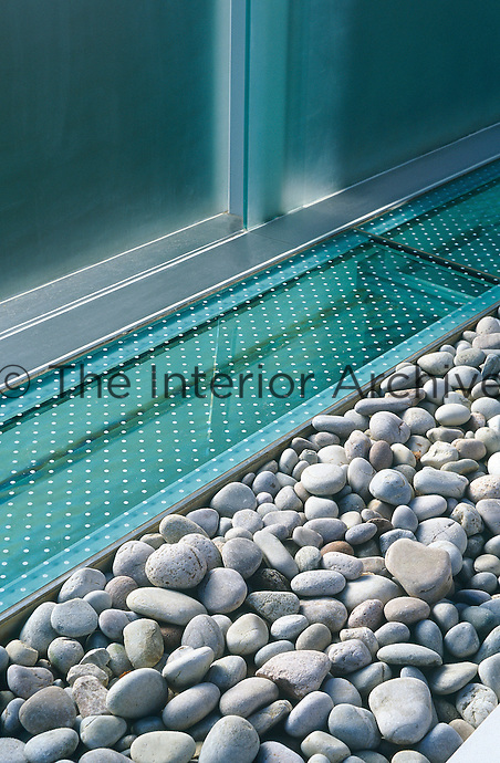 A detail of hardened sandblasted glass panels and s kylight edged with pebbles designed to let light into the room below