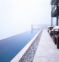 Infinity pool positioned along the edge of Table Mountain with a misty sea view.