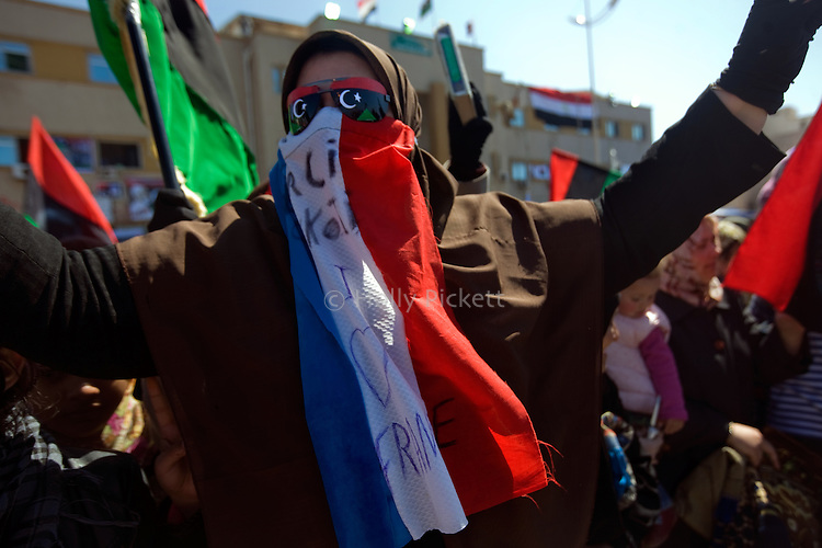 "A Libyan woman wears a French flag over her face which says ""Mercì Sarkozy, I love France"", in 17th of February Square, the center of the Libyan uprising, Benghazi, Libya, March 25, 2011. Residents expressed their gratitude to France and the Western Allies for halting the Qaddafi offensive on Benghazi with a barrage of air strikes enforcing the no-flight zone over Libya."
