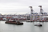 aerial photograph of a tug boat towing a loaded barge Port of Oakland, California