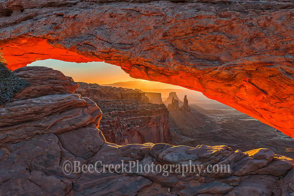 Window view of Mesa Arch at sunrise where you can see this soft glow as the sun was breaking the horizon and the underside of the arch began to glow with red highlights of the morning sun.  This is what  has made the arch so famous this glow on the underside and in the canyons.