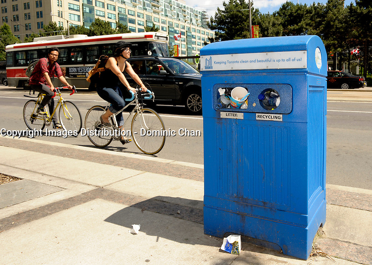Toronto (on) CANADA, July 4, 2009 Toronto Garbage Strike - full garbage can at Queensquay / Harbourfront area with TTC street car  and bicycles in the background. (no model release - editorial only)