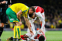 Christoph Zimmermann of Norwich City & Olivier Giroud of Arsenal check on injured Ainsley Maitland-Niles of Arsenal during the Carabao Cup match between Arsenal and Norwich City at the Emirates Stadium, London, England on 24 October 2017. Photo by Carlton Myrie.