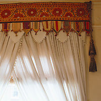 A length of colourful Indian fabric is recycled as a pelmet with simple white cotton curtains